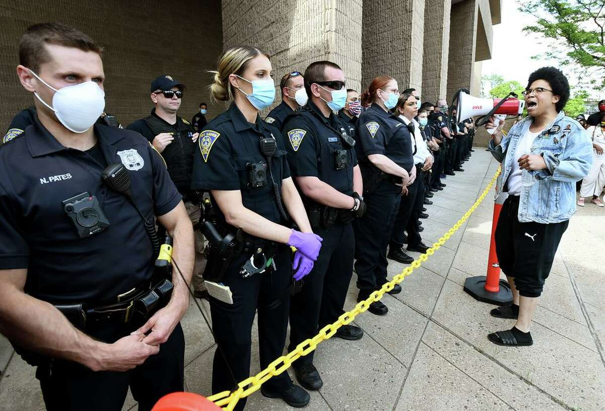 New Haven police officers stand in front of police headquarters during a protest May 31.
