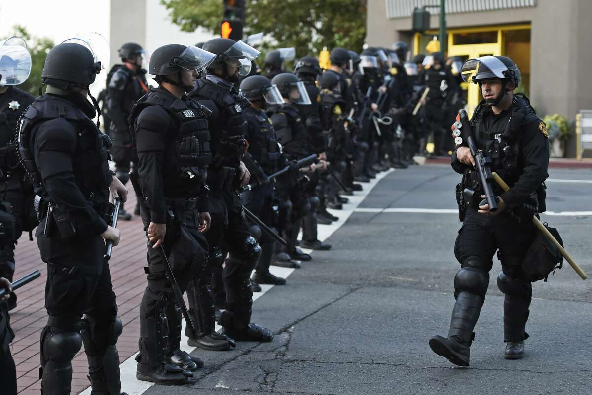 Police sweep the streets as looters march around downtown Walnut Creek, Calif., on Sunday, May 31, 2020.