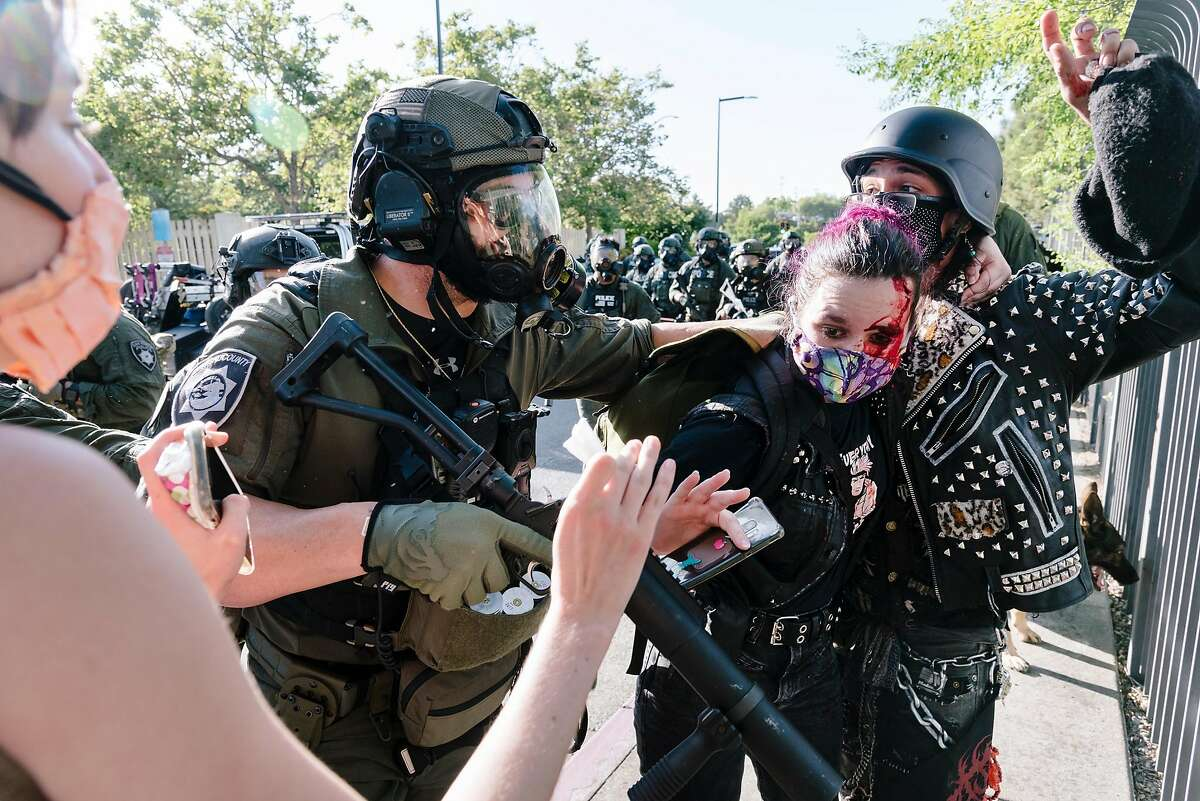 Police advance on protesters, including one that was hit in the head by a police projectile, after firing tear gas and non-lethal projectiles following a dispersal order near an entrance to Interstate 680 in Walnut Creek, Calif, on Monday, June 1, 2020.