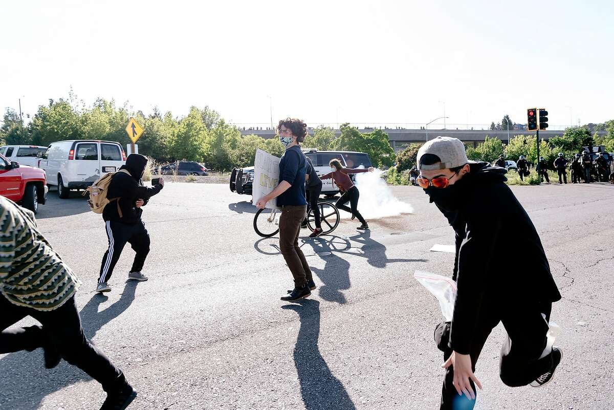 Protesters run as police blocking the entrance to Interstate 680 fire tear gas and non-lethal projectiles following a dispersal order, in Walnut Creek, Calif, on Monday, June 1, 2020.