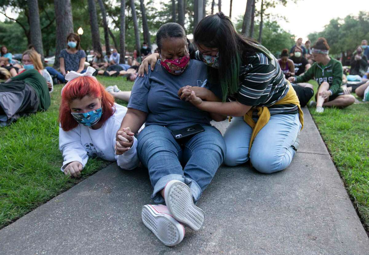Janet Collins, a criminal justice teacher at Kingwood High School, is consoled by two students as she cries during the silent moment for George Floyd, who died in Minneapolis Police Department custody a week ago, Monday, June 1, 2020, at Town Center Park in Kingwood. The event, which was organized by two Humble ISD teachers, invited participants to lay down silently for eight minutes and forty-six seconds to honor Floyd's life.