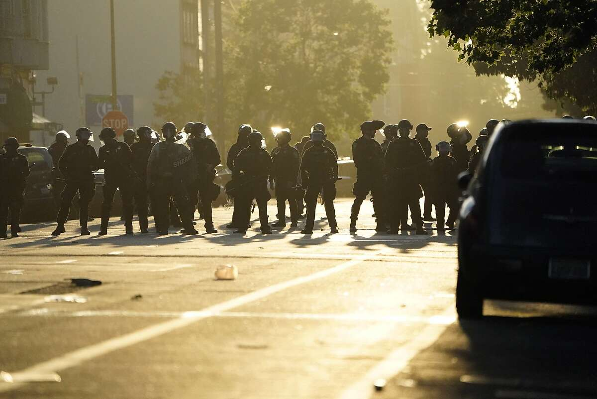 Police ready to enforce the curfew on Broadway on Monday, June 1, 2020 in Oakland, Calif.