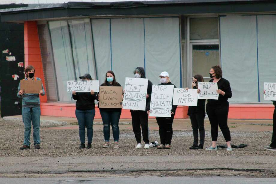 Protesters on Monday night held signs while some passersby honked their horns. Event organizer Melanie Bellamy said the event was in response to police brutality and was sparked by the death of George Floyd in Minnesota last week. (Michelle Graves/News Advocate)