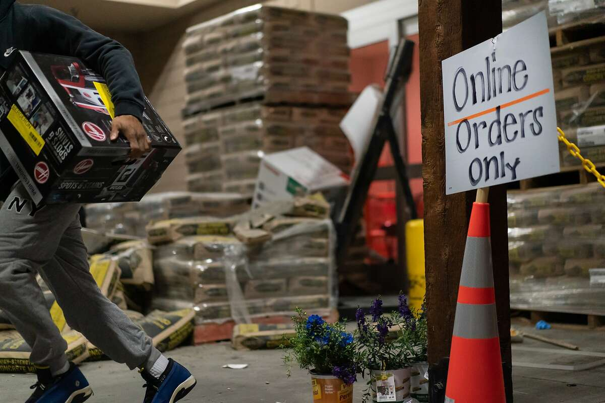 People removing items from a closed High Street Home Depot on Monday, June 1, 2020 in Oakland, Calif.