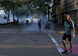 Demonstrators running from teargas used by the Oakland Police Department after a solidarity protest against police brutality and the killing of black citizens in Oakland, Calif., on Monday, June 1, 2020. Following days of protest against police brutality, some community members are calling to defund local police departments.
