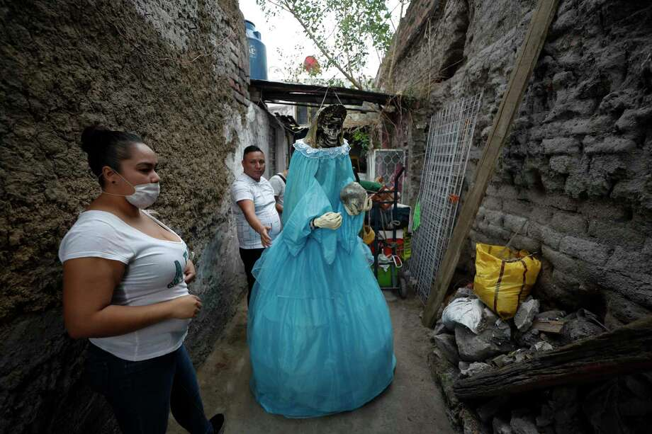 """Neighbors help to return a giant figure of the """"Santa Muerte,"""" or Death Saint, to a home, after it was displayed in the street to celebrate the saint's monthly festival day, which drew thousands of devotees despite the ongoing coronavirus pandemic, in Mexico City's Tepito neighborhood, Monday, June 1, 2020. Despite the ongoing coronavirus pandemic, thousands of devotees, few wearing face masks amidst the dense crowd, made the monthly pilgrimage Monday to pray or give thanks to Santa Muerte, one of several unofficial folk saints worshipped in Mexico. Photo: Rebecca Blackwell, AP / Copyright 2020 The Associated Press. All rights reserved."""