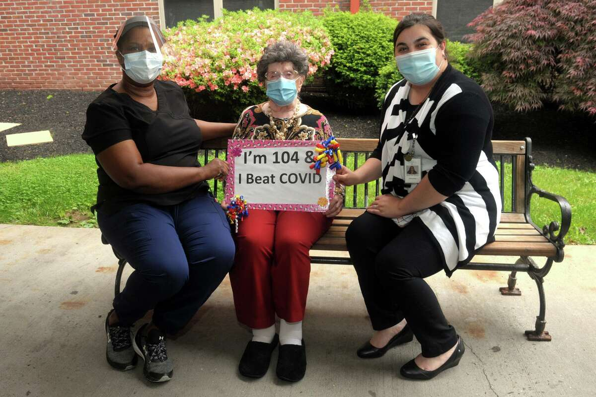 Lora Bartult, age 104, is joined by administrator Rite Lynch and admissions coordinator Jenny Dosantos in front of Maefair Health Care, in Trumbull, Conn. May 28, 2020. Bartult is has recovered after being diagnosed with coronavirus and is also a survivor of the Spanish Flu of 1918.