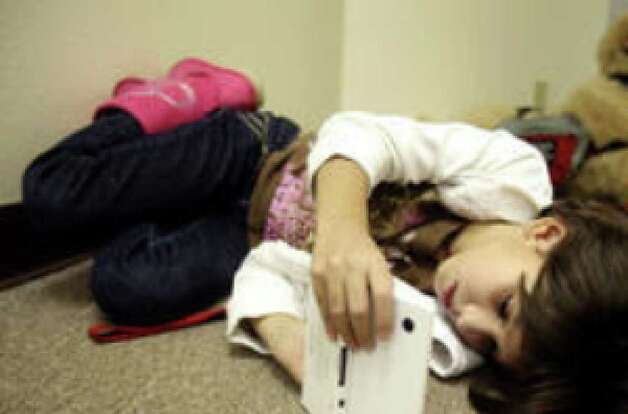Becca Major, 11, plays on her Game Boy  while her mother attends a recent support group meeting at the Epilepsy Foundation of Central and South Texas.