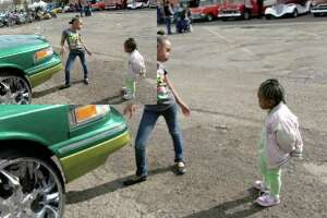 """Cheyanne Sommers, 8, and sister Zamora Sommers, 2, dance next to a 1996 Lincoln Town Car owned and shown by their dad, Andrew Sommers, during a car show that was part of """"A Brotherhood of Forces, Honoring Veterans Past and Present"""" at VFW Post 76."""