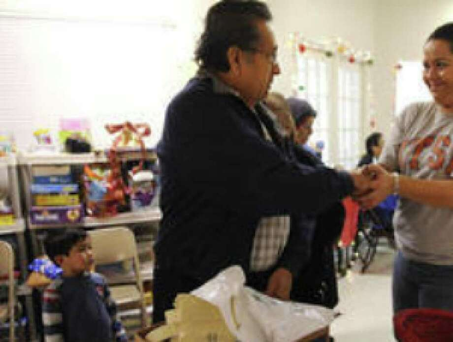 Gonzalo M. Garza shakes the hand of Elizabeth Rodriguez, Merced Housing's resident services coordinator, after receiving food Friday at Merced's Avion Place Apartments.