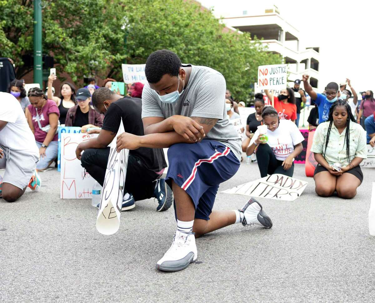 A demonstrator kneels for a moment of silence in honor of George Floyd in downtown Conroe, Sunday, May 31, 2020. Approximately over 100 people participate in the demonstration.