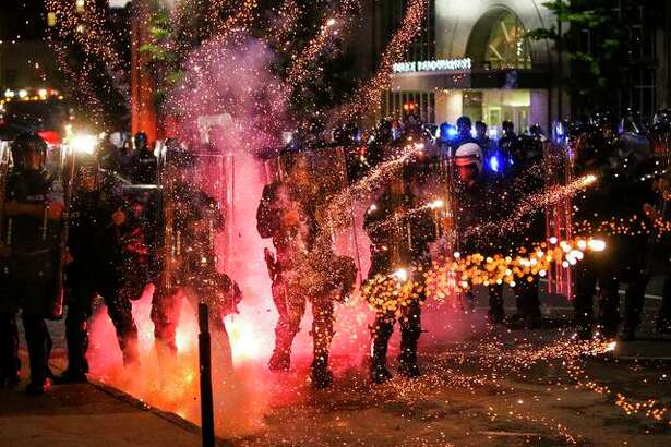 Fireworks go off in front of police, who with protesters in front of police headquarters in St. Louis on Monday, June 1, 2020. The small group of protesters was originally part of a much larger group demonstrating earlier in the afternoon against the death of George Floyd.