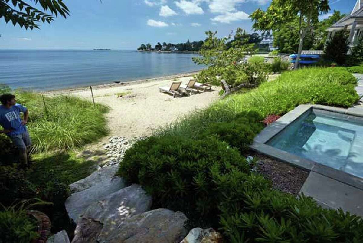 The back of the house faces Long Island Sound and features a covered porch, patio, a 72-square-foot hot tub, and private beach.