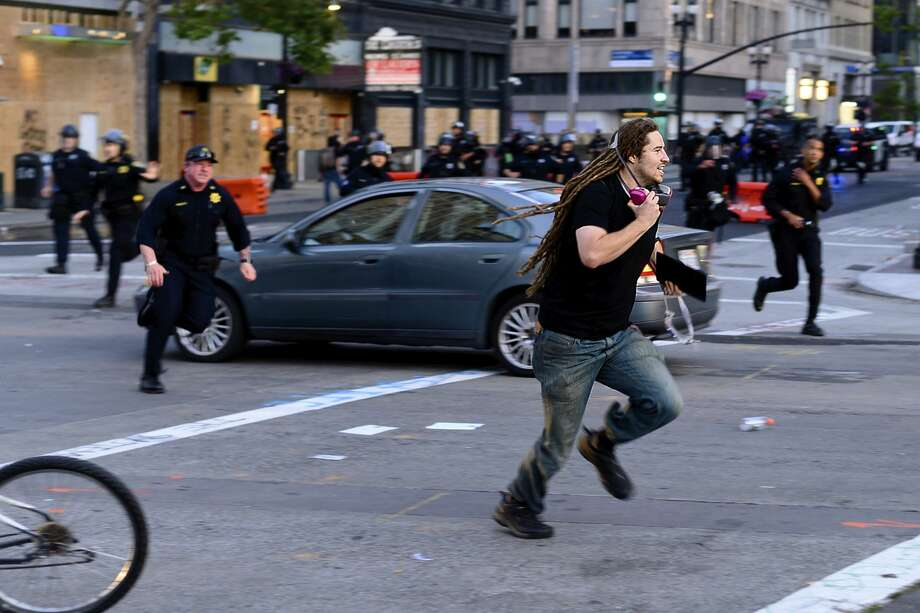 A man runs from police officers in Oakland, Calif., Monday, June 1, 2020. Photo: Noah Berger/Associated Press