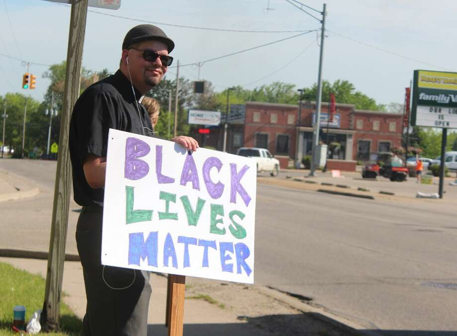 Rev. JT Hills and Devon Herrell stood outside the United Church of Big Rapids Tuesday morning, protesting in support of the Black Lives Matter movement. Photo: (Pioneer Photos/Catherine Sweeney)
