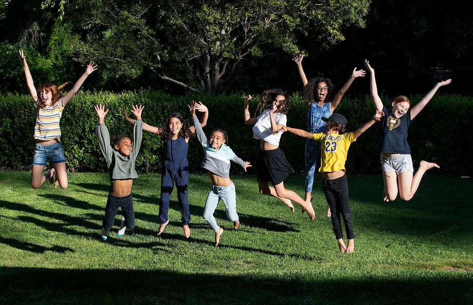 """The students of """"Brothbush Academy"""" cheer for their home school on the Roth's front lawn in the midst of the coronavirus pandemic on May 5, 2020 in Riverside, Calif. From left, Kat Bristow, Andie Bristow, Rosie Roth, Allison Furbush, Penelope Roth, Sylvester Roth, Carmen Furbush, and Ellie Bristow. (Gina Ferazzi/Los Angeles Times/TNS) Photo: Gina Ferazzi, TNS"""