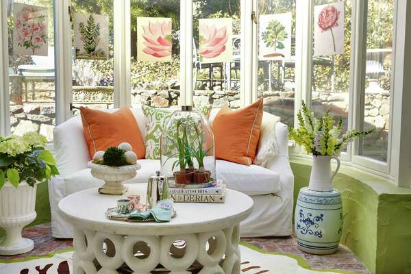 """Carey Karlan, owner of Last Detail Interior Design in Darien, considers her home's conservatory - with its larger outdoor planters, garden stools, terrarium, indestructible indoor/outdoor coffee table, green garden-like etagere, botanicals, and pitchers of flowers - a summer retreat. """"I have coffee here every morning,"""" she says."""