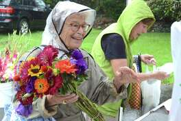 Longtime New Canaan resident Jeannie Hart makes a flower purchase at the weekly New Canaan Farmers Market in 2018.