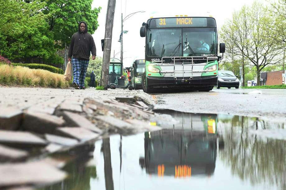 One of the DDOT buses sits near Ascension St. John Hospital in Detroit on May 18, 2020. At left is bus rider Raymoan Autrey, 48, who took the bus to do some shopping and return home. (Robin Buckson/The Detroit News/TNS) / The Detroit News
