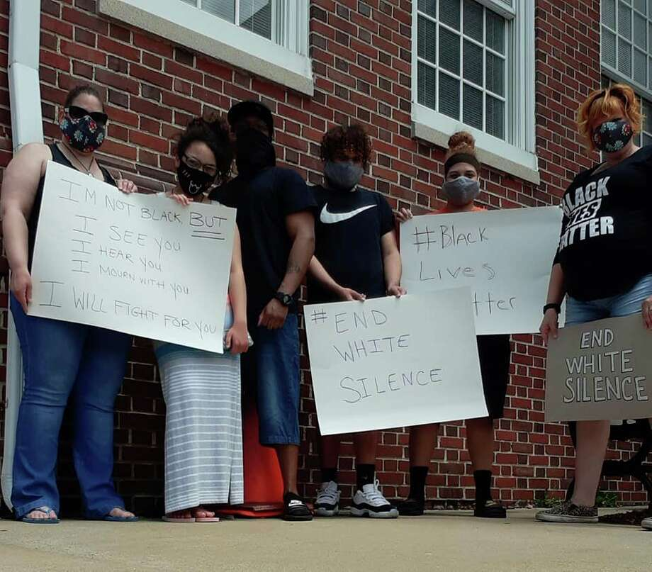 A photo from theShowing Up for Racial Justice Facebook page shows a group of protesters holding signs supporting the #BlackLivesMatter movement. (Courtesy Photo)