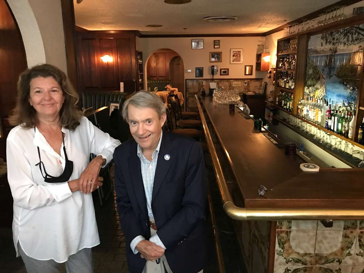 . Owners and proprietors Geoffrey and Anne Trimble pose in front of the bar with Albany Mayor Erastus Corning 2nd shortly after the 1977 opening (Provided photo) ... Anne Trimble, 71, with longtime La Serre Jay Donnaruma, a retired stockbroker, pose at the bar last week after an afternoon of reminiscing about the colorful cast of characters during its 43-year run (Paul Grondahl / Times Union) ... Jay Donnaruma points to a sketch of La Serre that hung near the bar for decades at La Serre as owner and co-manager Anne Trimble looks on. (Paul Grondahl / Times Union)