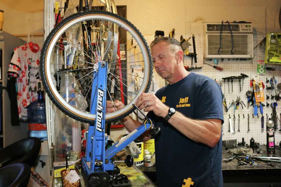 Jeff Currier of the Slow TwitchNiche bicycle repair shop in Seabrook trues a wheel. He started a program four years ago to repair and give away bikes, and residents have donated hundreds to his program each year. Photo: John DeLapp / , Correspondent