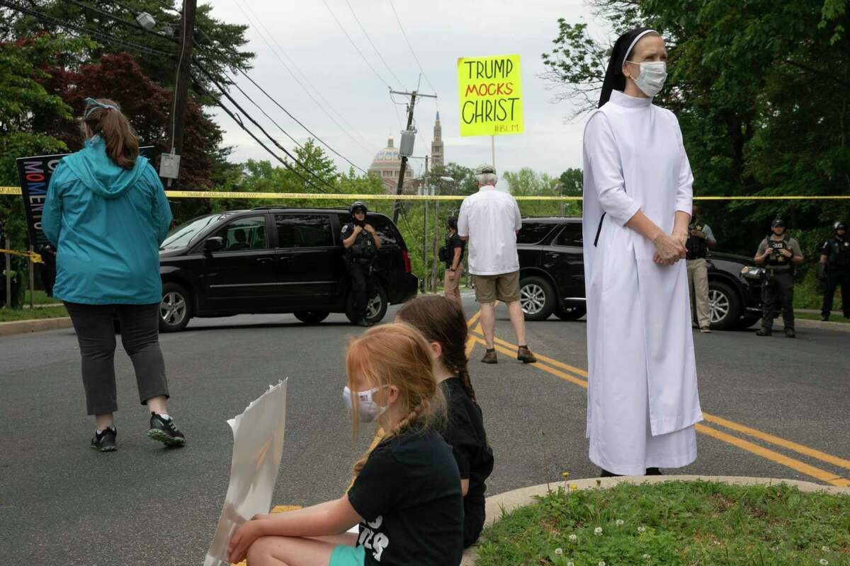 Sister Quincy Howard, right, a Dominican nun, arrives to protest the arrival of President Donald Trump to the Saint John Paul II National Shrine, Tuesday, June 2, 2020, in Washington. Many demonstrators said they were dismayed when Trump staged a visit to the historic St. John's Church across from the White House and held up a Bible after authorities had cleared the area of peaceful protesters.