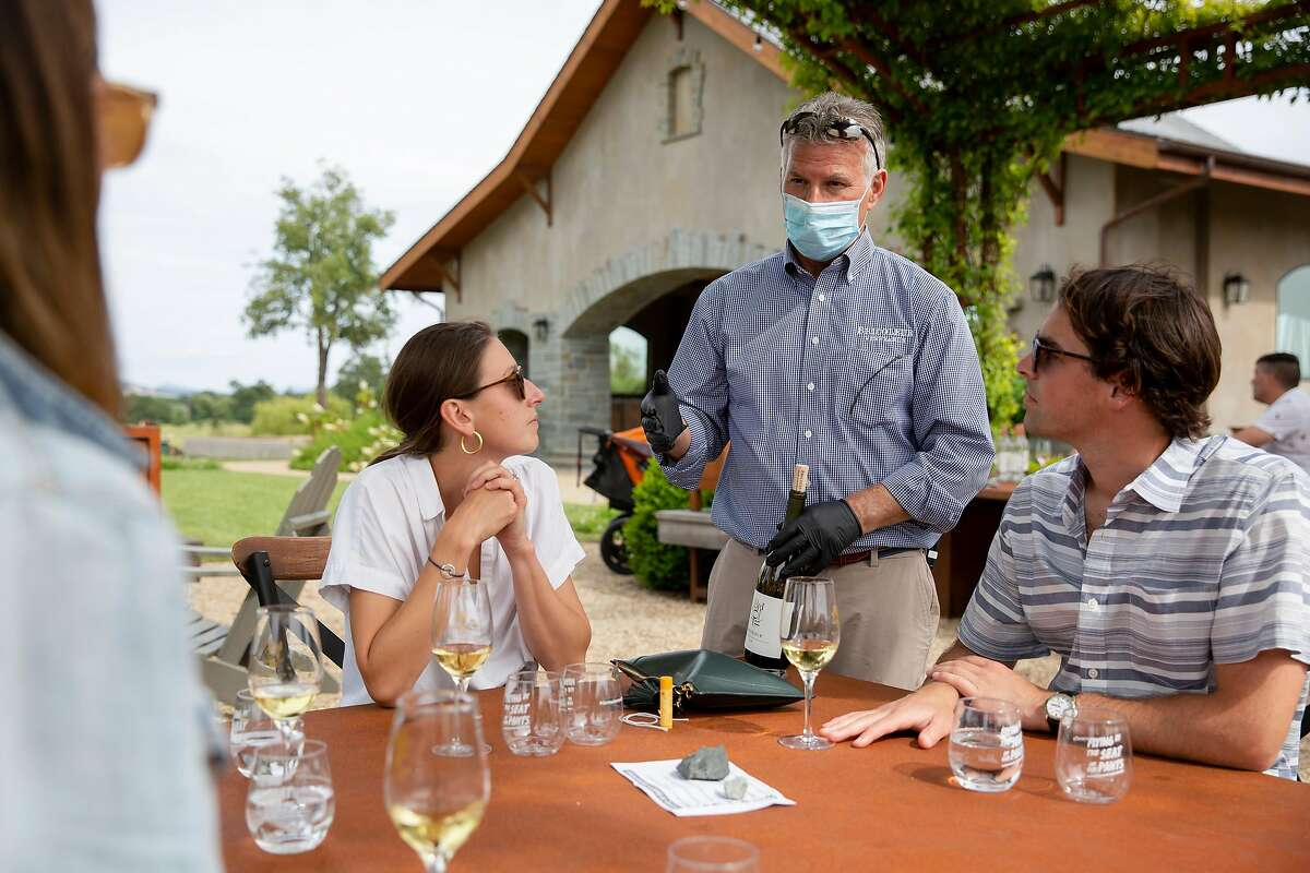 Mark Hanson, owner of Bricoleur Winery, talks with patrons as they taste wine at Bricoleur Winery in Windsor, Calif. on Sunday, May 31, 2020.