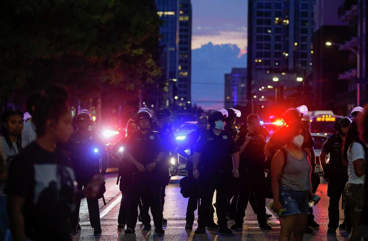 Houston Police officers block off a street during a protest May 30, 2020, in downtown Houston. Demonstrators marched to protest the death of George Floyd, who died while in custody of Minneapolis Police last Monday night. Behind the officers is one of the Metropolitan Transit Authority buses used to ferry riot-clad officers around the central business district.