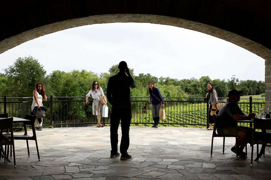 Visitors pose for a photo in the stone pavilion, the work of Healdsburg stone mason Domenichelli Masonry. Photo: Brittany Hosea-Small / Special To The Chronicle