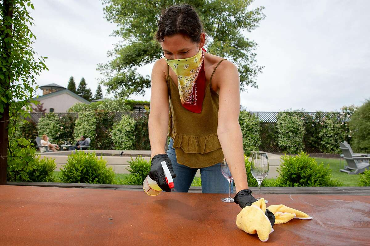 Shelby Greeley disinfects a table after guests had a wine tasting at Bricoleur Winery in Windsor, Calif. on Sunday, May 31, 2020.