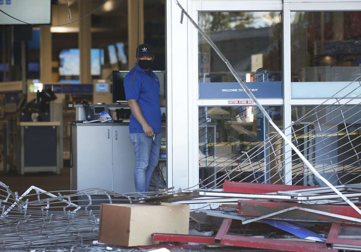 An employee surveys the damage at a Best Buy store in Fairfield, Calif. on Tuesday, June 2, 2020 the morning after looters broke into the store and stole electronic equipment one week after George Floyd was died in police custody in Minneapolis.