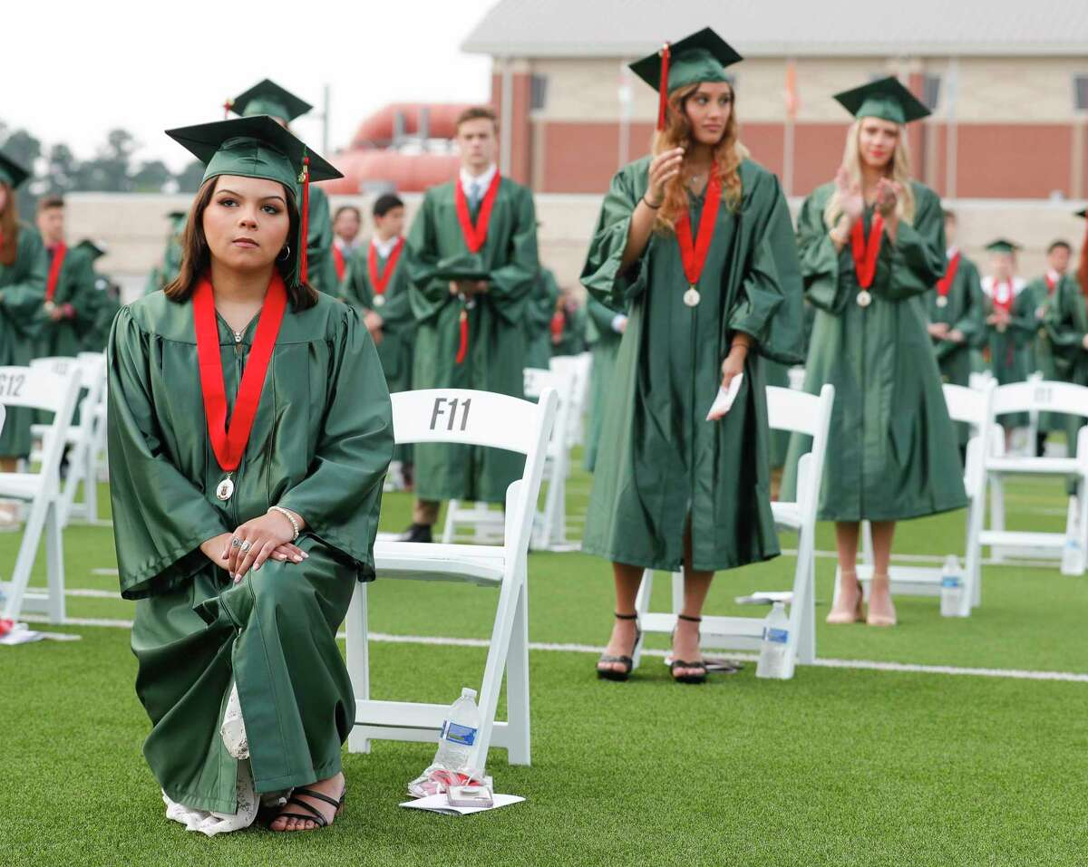 Kiara Altieri kneels as the national anthem plays during The Woodlands High School's graduation ceremony at Woodforest Bank Stadium, Tuesday, June 2, 2020, in Shenandoah.