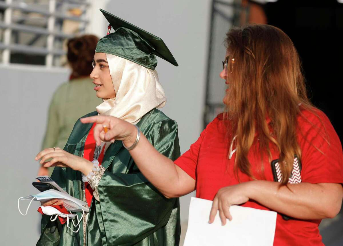 Fatima Hasan gets help finding her seat before The Woodlands High School's graduation ceremony at Woodforest Bank Stadium, Tuesday, June 2, 2020, in Shenandoah.