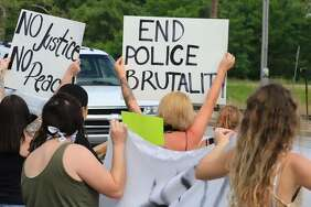 Members of a peaceful rally Monday afternoon hold signs outside the Alton Police Station. Local officials are unsure why Gov. J.B. Pritzker included Madison County as only one of nine counties in a disaster declaration Monday because of civic unrest.
