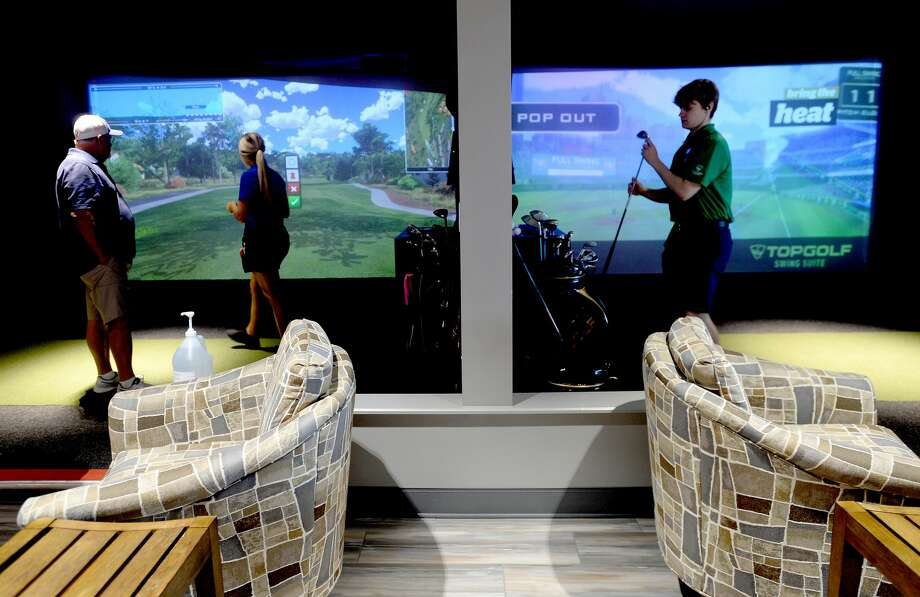 Leanna Bishop runs through instructions on using the simulated indoor golf stations with guests Mike Melancon, Paul Patin and Randall Burt at 5 Under Golf Center in Beaumont Friday, May 22. Photo taken Friday, May 22, 2020 Kim Brent/The Enterprise Photo: Kim Brent/The Enterprise