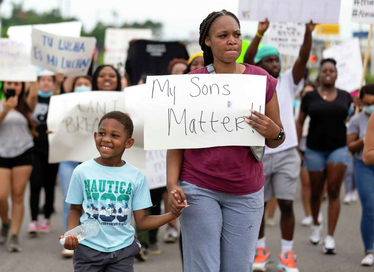 A mother and son walk down 105 during a protest against police brutality in Conroe, Sunday, May 31, 2020. Approximately over 100 people participate in the demonstration.