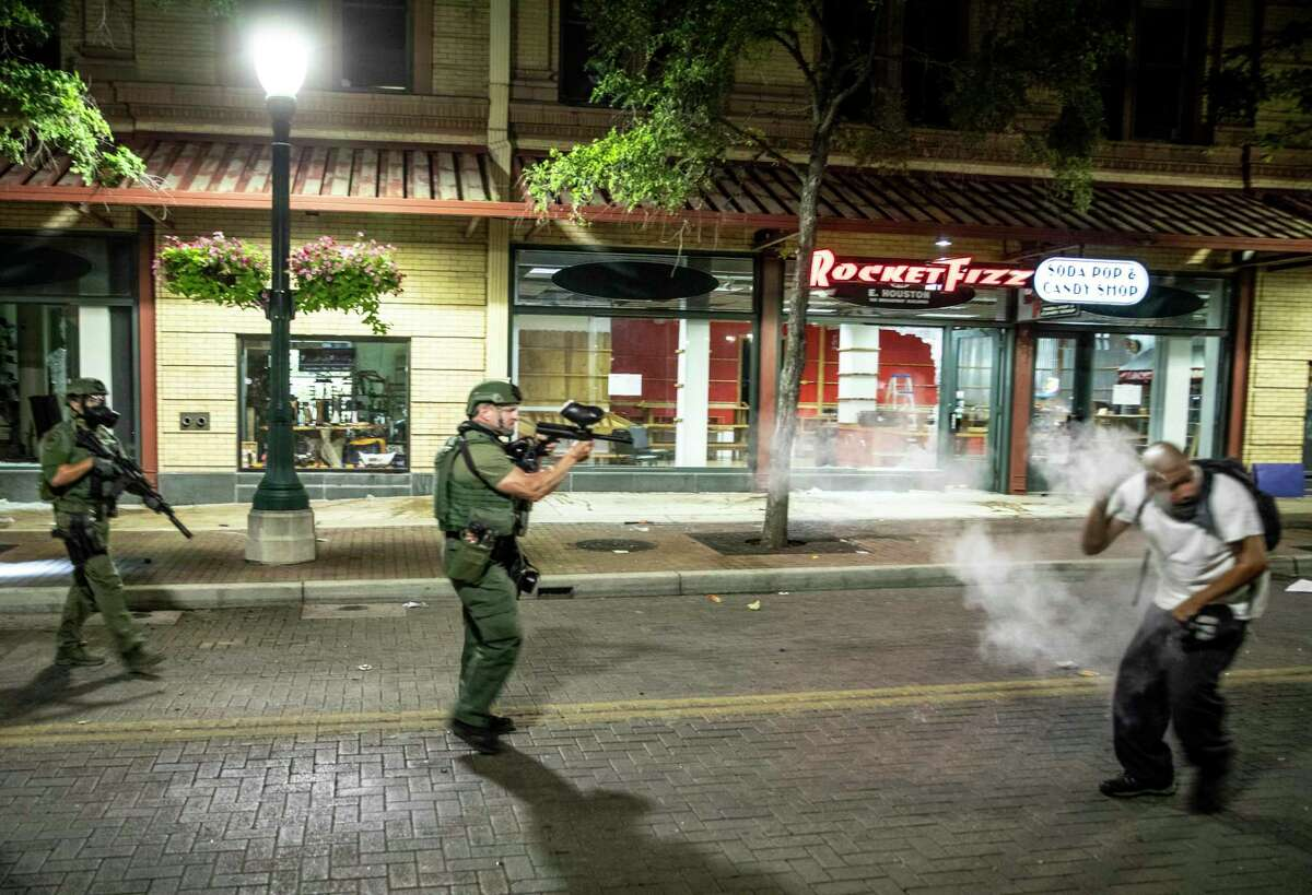 A man, right, is shot with pepper balls by a San Antonio Police Officer after the man looted Mar Imports jewelry store on Houston Street in downtown San Antonio, Texas, U.S. on Saturday, May 30, 2020. People took to the streets of San Antonio to protest the killing of George Floyd in Minnesota while he was in police custody. Looting took place in downtown Houston street as police fired tear gas and pepper balls at protestors as they looted stores.