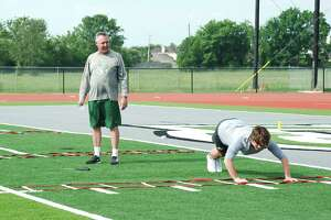 Lutheran South Academy football coach Don Justice watches as Cade Goldstraw participates in a drill during summer conditioning camp.