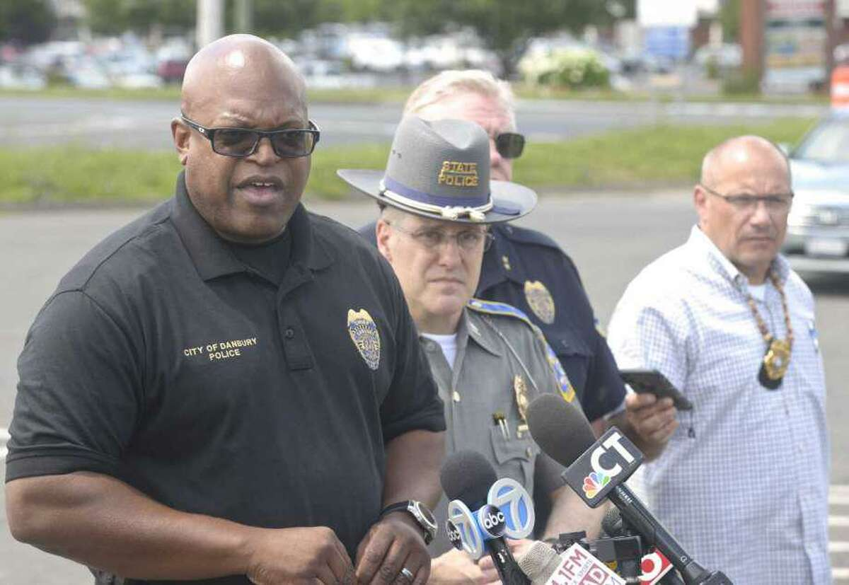 Police Chief Patrick Ridenhour ,left, speaks at a press conference, in the I-84 exit 2 commuter parking lot, about an officer involved shooting that happened July 3, 2019, in Danbury, Conn.