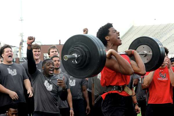 Lamar's teammates get in the spirit as Marcellus Johnson makes his next lift during the football team's annual Night of Champions weightlifting event on the football field Tuesday night. Photo taken Tuesday, April 30, 2019 Kim Brent/The Enterprise