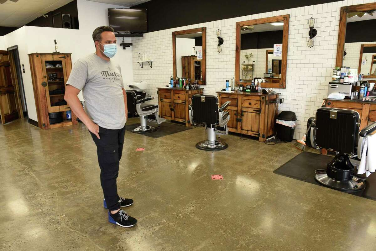 Joey Federico, owner of The Barber Parlor, has distance markers on the floor and signs on mirrors to wear masks as he prepares to open for business on Tuesday, June 2, 2020 in Albany, N.Y. Barber shops are one of the businesses that are allowed to re-open Wednesday after having to close due to COVID-19 pandemic. (Lori Van Buren/Times Union)