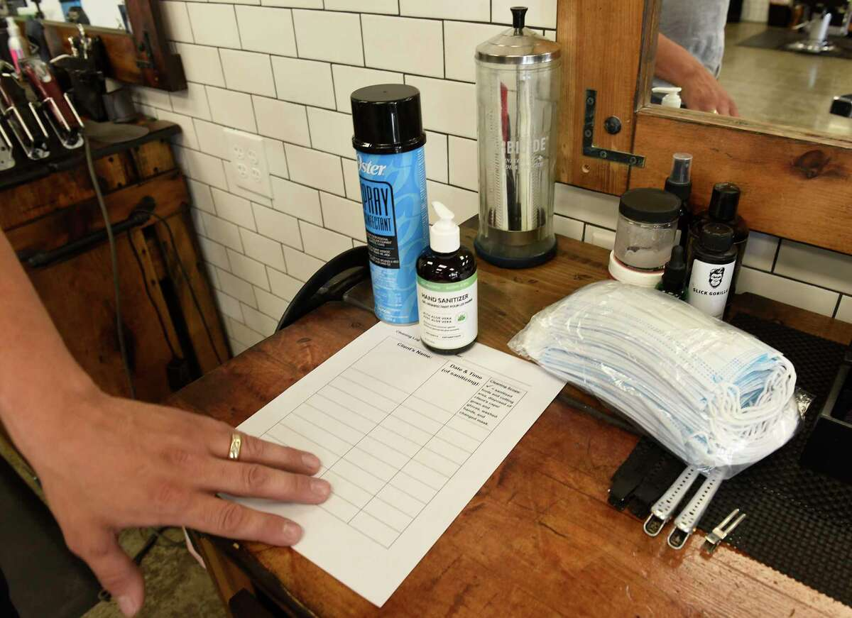 Joey Federico, owner of The Barber Parlor, makes sure each barber station has PPE and safety check list as he prepares to open for business on Tuesday, June 2, 2020 in Albany, N.Y. Barber shops are one of the businesses that are allowed to re-open Wednesday after having to close due to COVID-19 pandemic. (Lori Van Buren/Times Union)