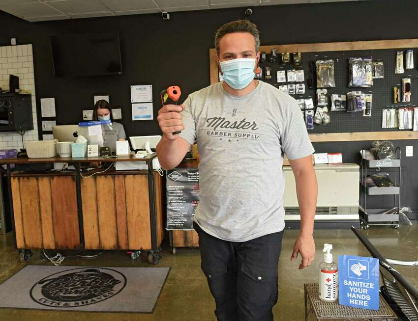Joey Federico, owner of The Barber Parlor, holds an infrared thermometer gun at the entrance of his shop as he prepares to open for business on Tuesday, June 2, 2020 in Albany, N.Y. Barber shops are one of the businesses that are allowed to re-open Wednesday after having to close due to COVID-19 pandemic. (Lori Van Buren/Times Union)