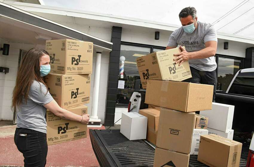 Joey Federico, owner of The Barber Parlor, right, and Ashleigh Goss, operations manager and barber, unload supplies as they prepare to open for business on Tuesday, June 2, 2020 in Albany, N.Y. Barber shops are one of the businesses that are allowed to re-open Wednesday after having to close due to COVID-19 pandemic. (Lori Van Buren/Times Union)