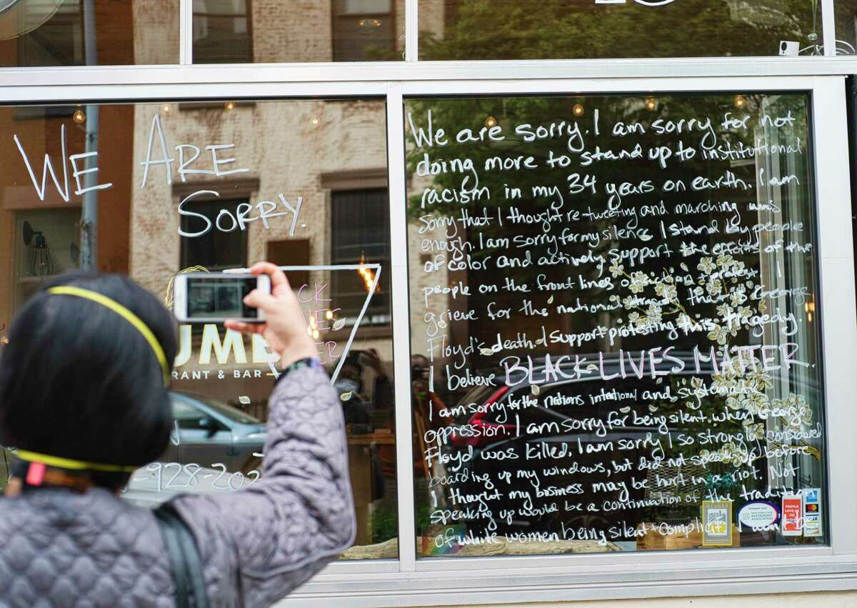 A woman takes a photo of a message written on the front window of the Plum Oyster Bar on Tuesday, June 2, 2020, in Troy, N.Y. (Paul Buckowski/Times Union)