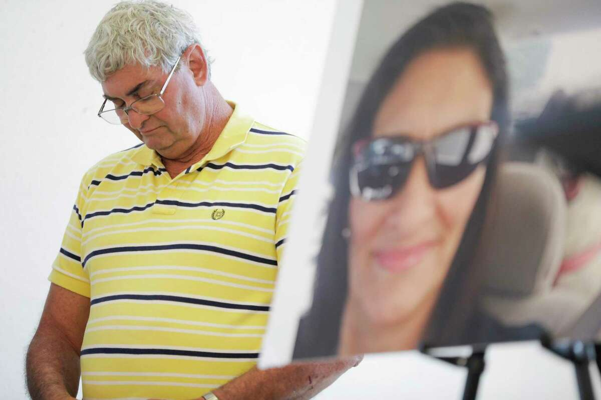 John Nicholas, brother of Rhogena Nicholas, lowers his head next to a photo of his sister during a press conference on Thursday, July 25, 2019 in Houston.