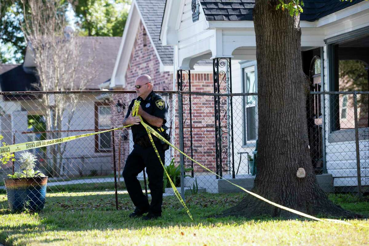 An officer takes down crime scene tape on Harding Street where two Houstonians were shot to death during a botched drug raid in January 2019.