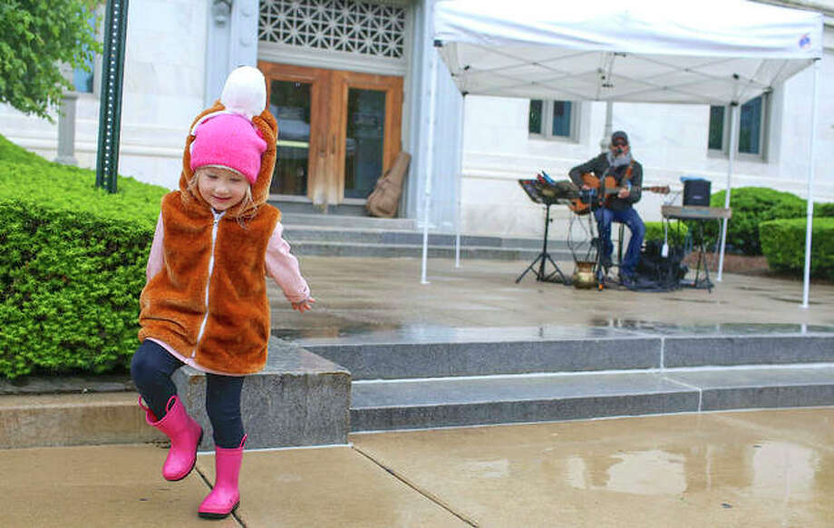 Valerie Van Daley, 4, dances and splashes in puddles while listening to local musician Butch Moore play some tunes last year at the Goshen Market in Edwardsville. Photo: Marci Winters-McLaughlin | Intelligencer File Photo