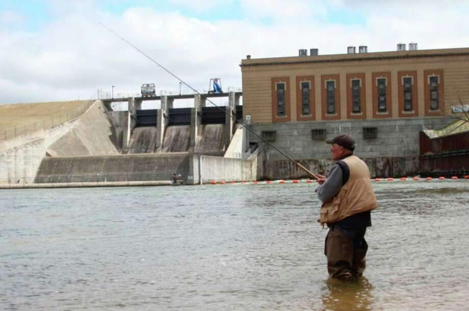 "An angler pictured fishes near Tippy Dam in April 2018. According to Mark Breederland, of Michigan Sea Grant Extension, ""The Manistee River certainly has been impacted by the dams that have been in there for a long time. There's stories about fishermen putting perch up and over the dams so that perch can reproduce farther upstream. (They used) buckets. I've got copies (that show) that from the 1940s."" (File photo)"